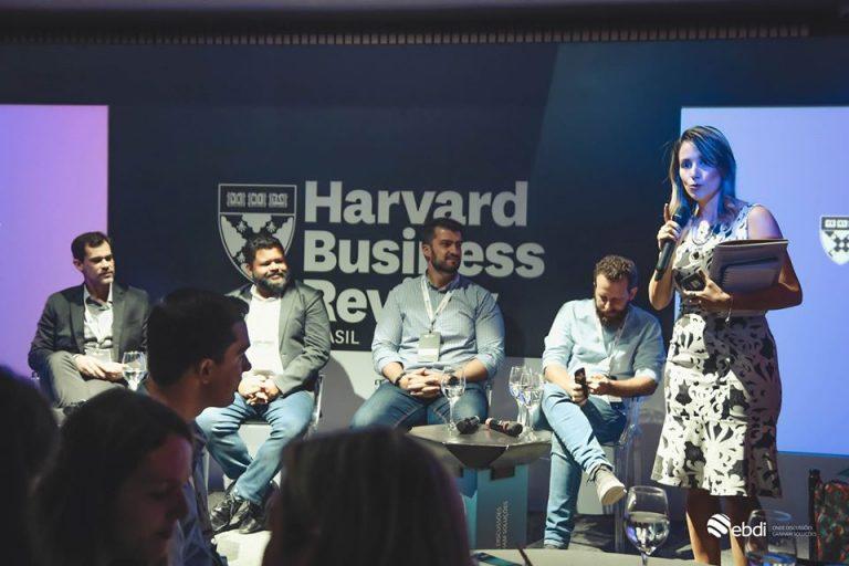 Encontro corporativo sobre data analytics em parceria com a HBR BR, no palco esta acontecendo um painel de debates com três executivos