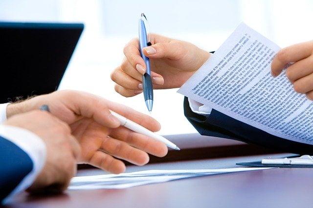 Duas pessos, de diferentes áreas em treinamento com uma caneta assinando um contrato. Um representa a pessoa de Compliance e o outro de Comercial