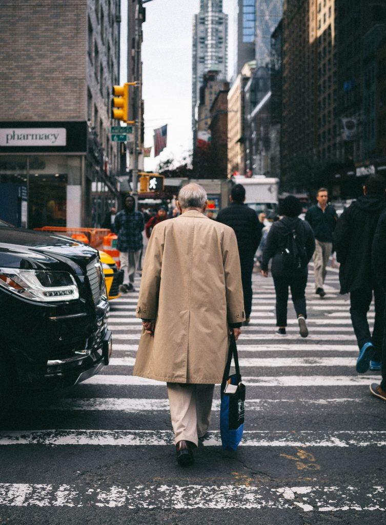 imagem representando o aumento e envelhecimento da população, há um homem idoso atravessando a rua em meio a cidade