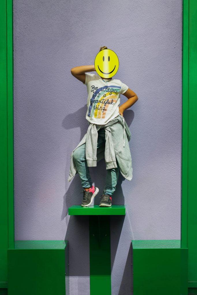 menina em cima de um pedestal com uma mascara de smile no rosto representando o foco no cliente, para o artigo além de clientes, sua marca possui embaixadores